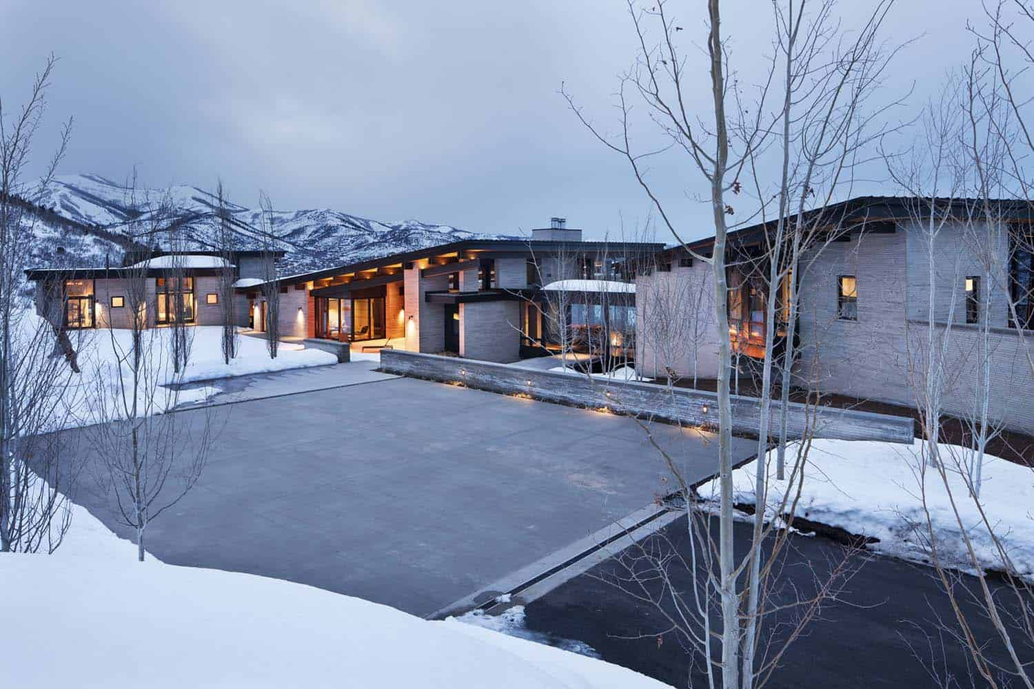 Majestic mountain home of stone and glass dominates its for Mountain architects