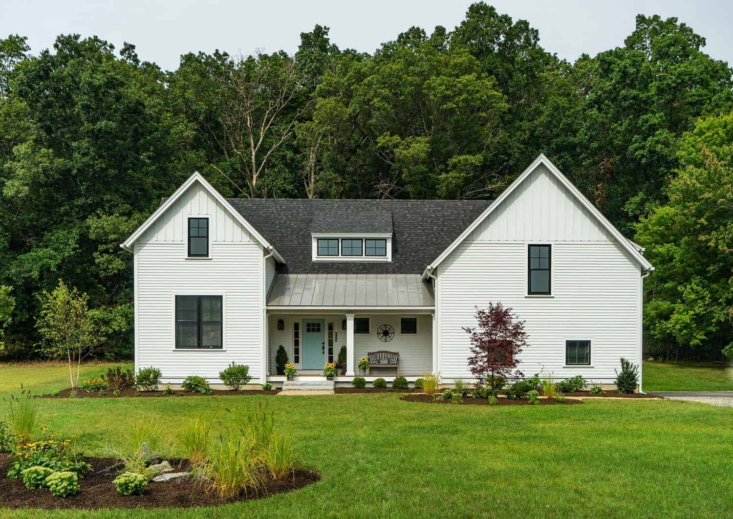 Modern farmhouse style nestled in an idyllic woodsy new for Modern new england home plans