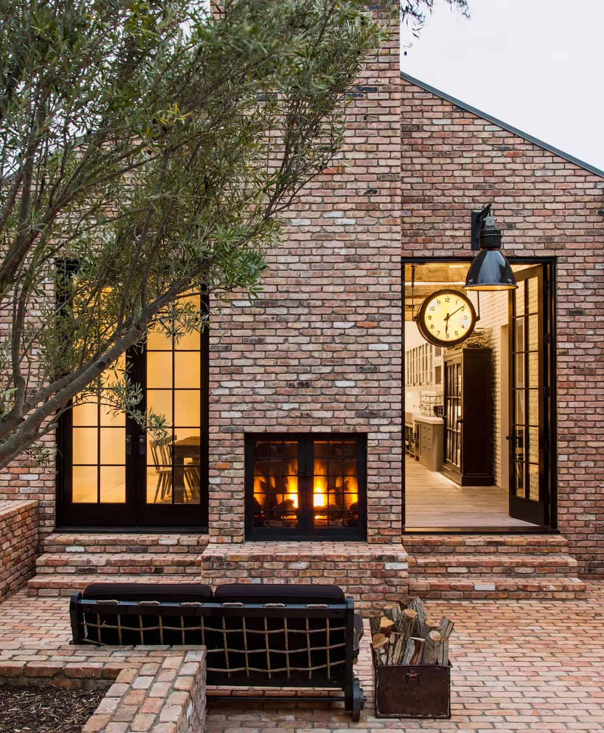 outdoor-patio-with-a-fireplace-on-a-brick-home-exterior