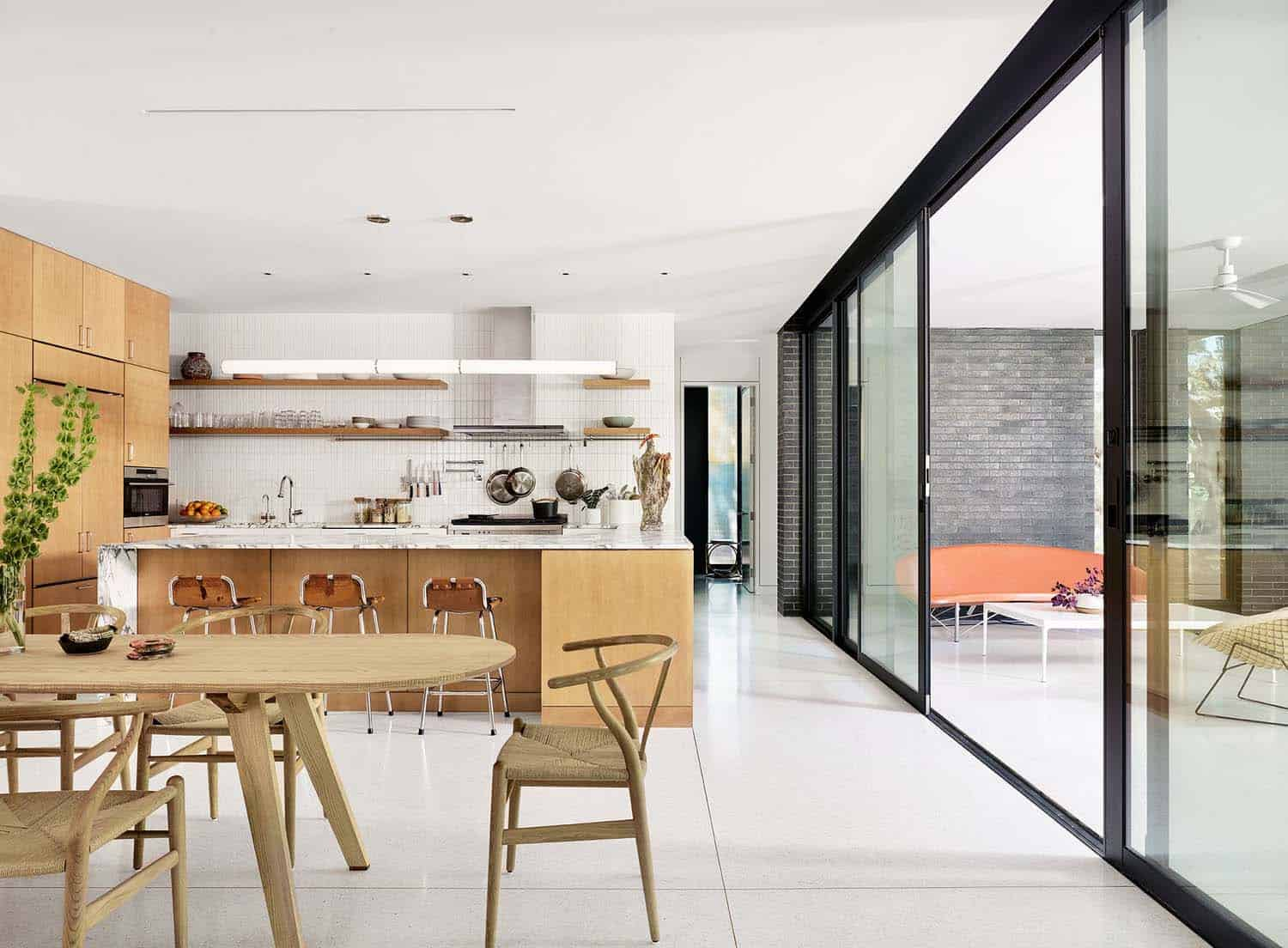 Above the kitchen features honed marble countertops and a handcrafted glazed ceramic tile backsplash the barstools are vintage by charlotte perriand