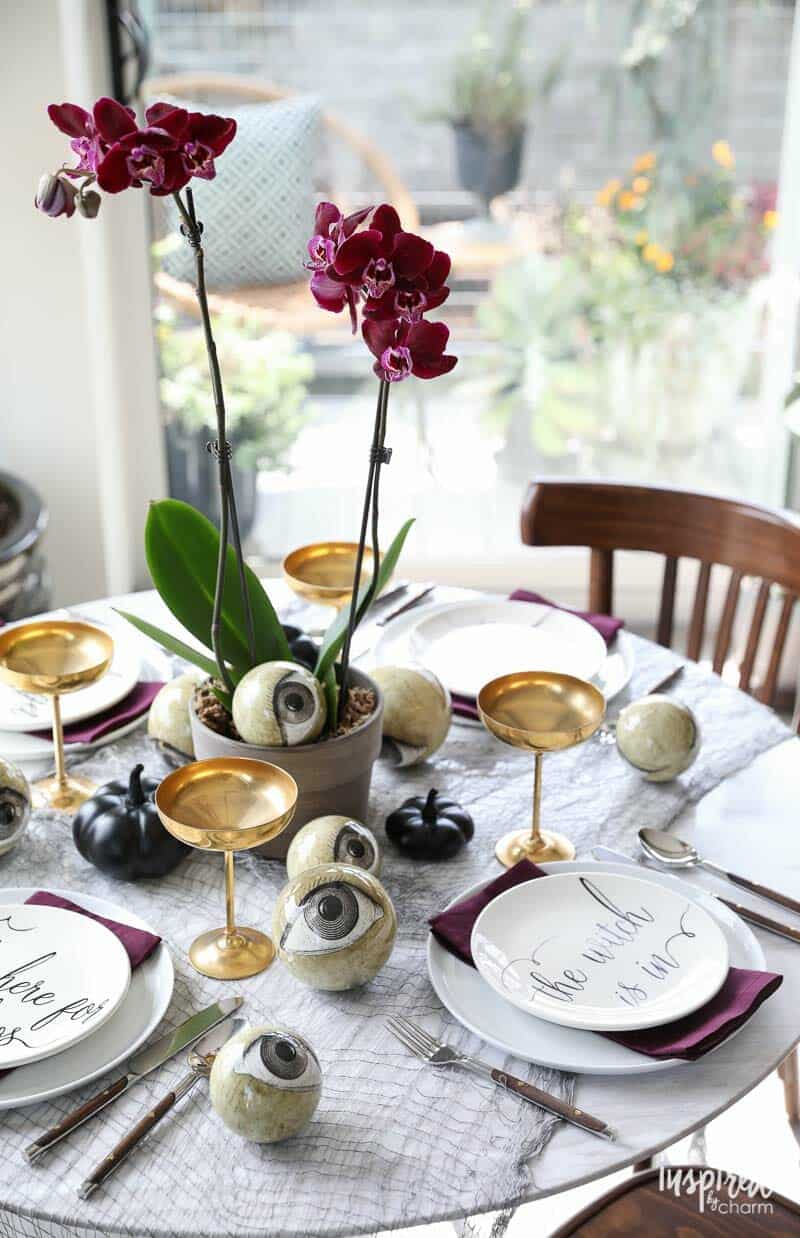 This Wicked And Eclectic Tablescape Features A Single Potted Deep Purple  Orchid For The Centerpiece. The Final Touch Is A Sprinkling Of Black Metal  Pumpkins ...
