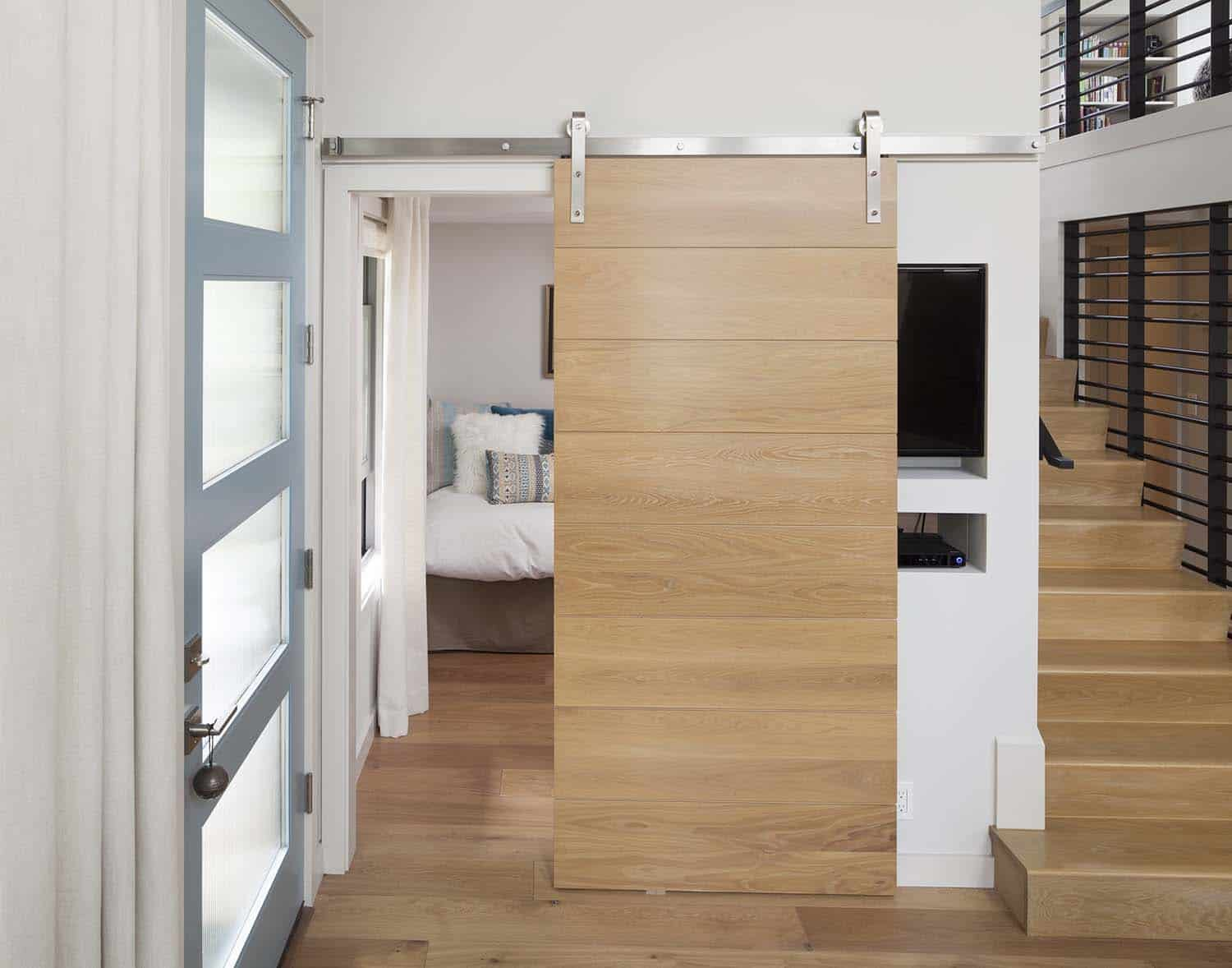 guestroom-with-barn-door-covering-entertainment-center-hall