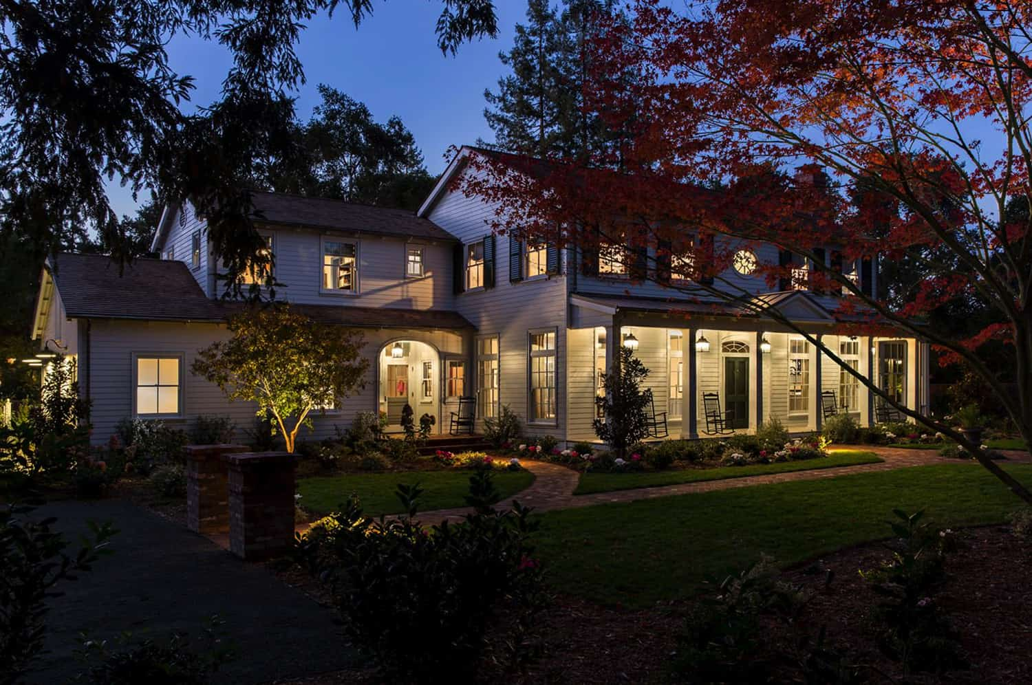 front-facade-and-yard-with-brick-paved-walkways-at-night-traditional-house-exterior