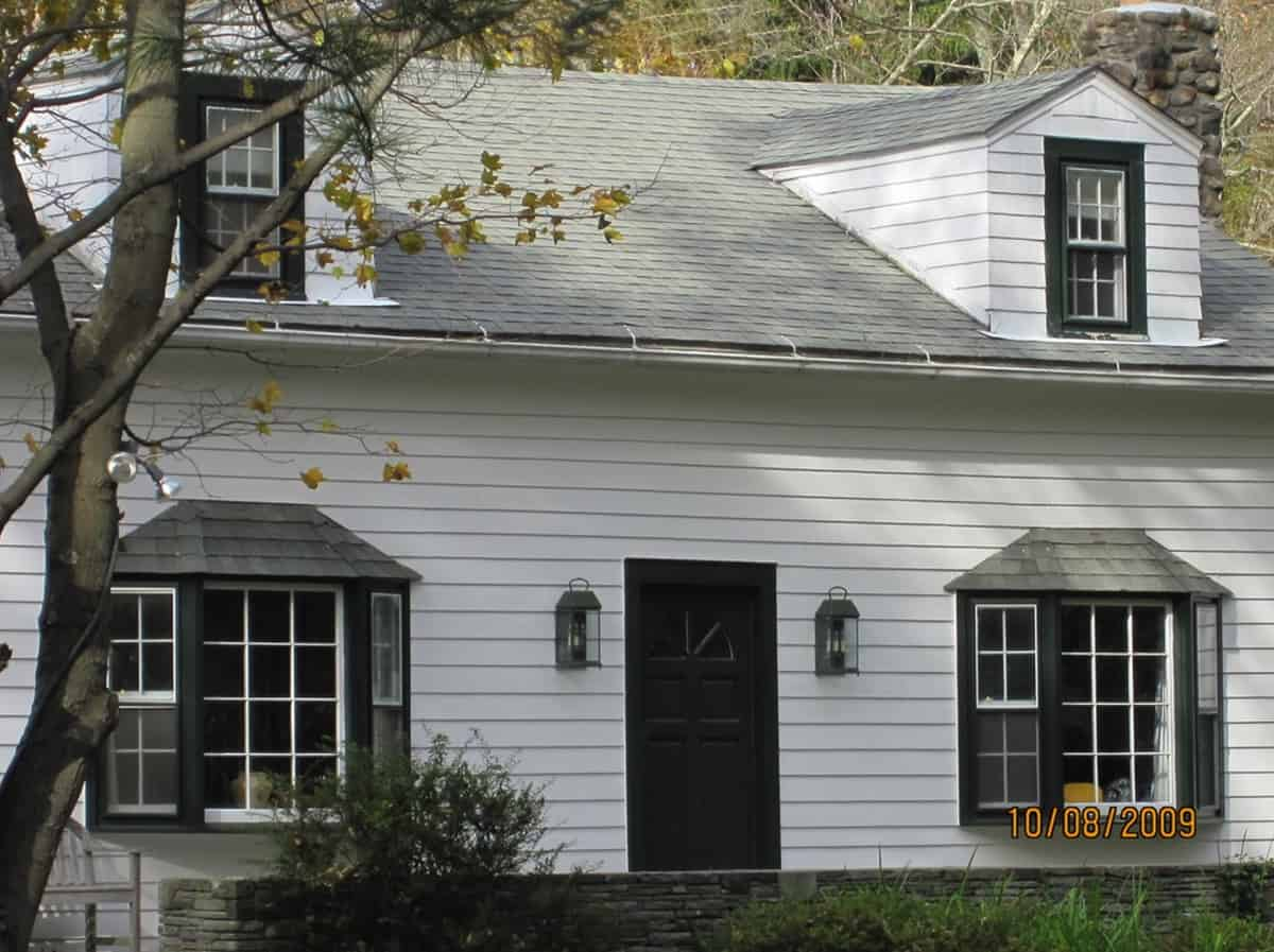 traditional-country-house-exterior-with-white-siding-and-dormer-windows-and-a-black-door-before-the-renovation