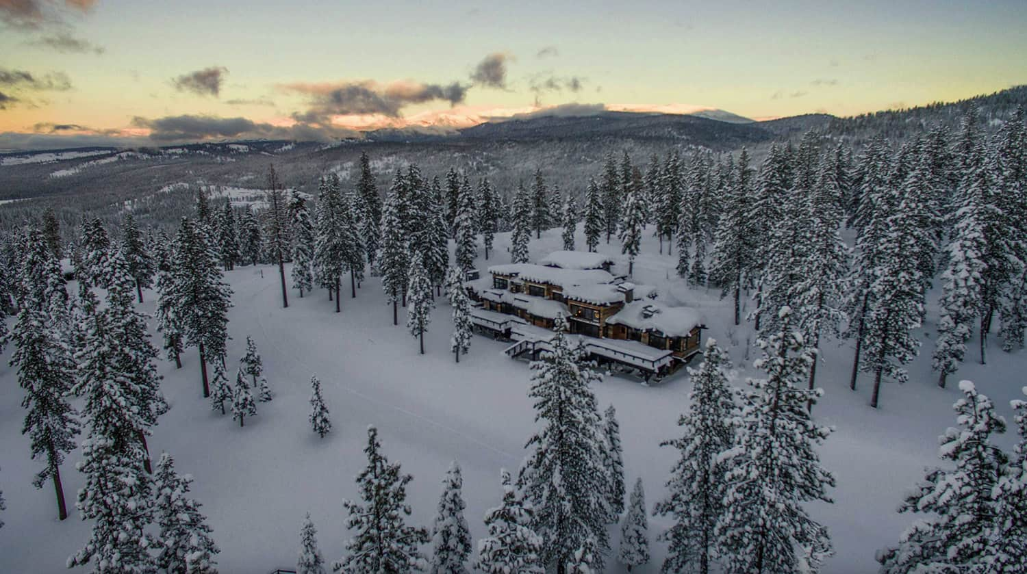 rustic-contemporary-mountain-home-exterior-aerial-view-with-snow